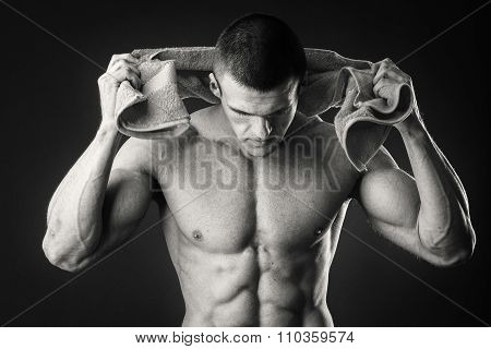 Bodybuilders with a towel on a dark background.
