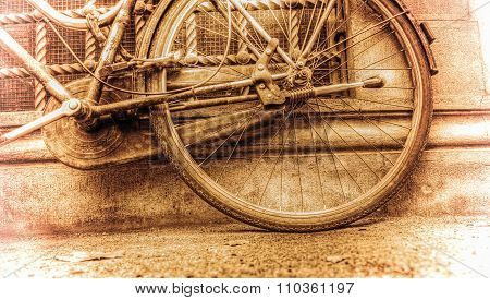 Old Bicycle Rear Wheel Against A Rustic Wall In Sepia Tone