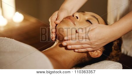 Relaxing woman having a massage for her skin on a face in salon