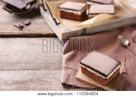 Delicious chocolate brownies on tray, on wooden background