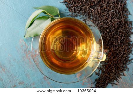 Glass cup of tea with green leaves and scattered tea around on blue wooden background