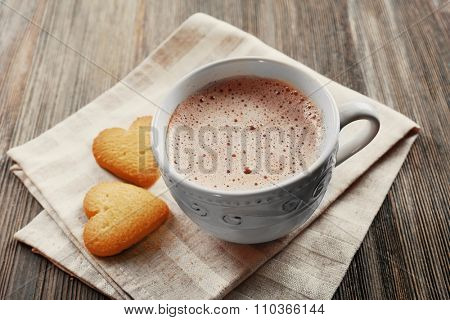 Cup of hot cacao with heart shaped cookies on cotton serviette