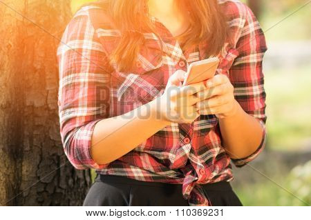 Young woman in red plaid shirt with smartphone. Unrecognizable person