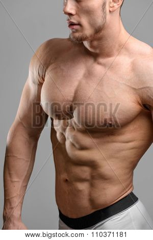 Close up shot without face of athletic man over grey background