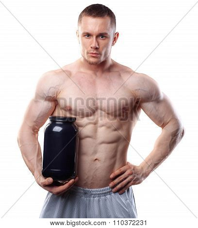 Bodybuilder holding a black plastic jar with whey protein isolated on white background
