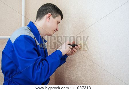 Worker Electrician Installs An Electrical Outlet