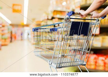 Woman Pushing Shopping Cart In Supermarket