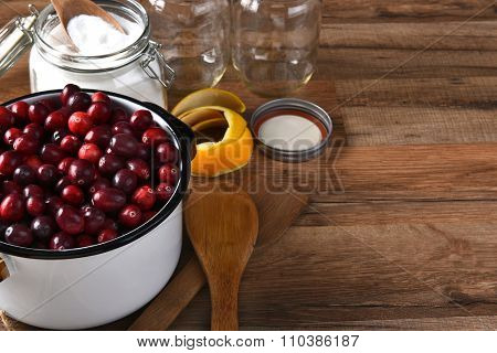 A pot of fresh cranberries surrounded by empty canning jars and bowl of sugar and utensils. Horizontal format with copy space.