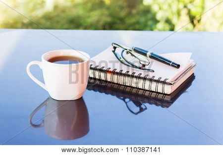 Classic White Cup Of Black Coffee Decorated With Note And Pen With Green Nature Background