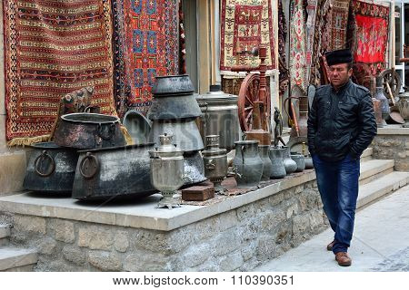 Trader selling traditional metal pots and carpets, in Baku's Old City.