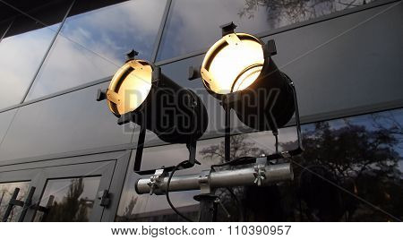 Accent spotlights on tripod over glass wall