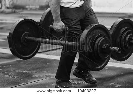 Lifting weights standing. Athlete takes deadlift.