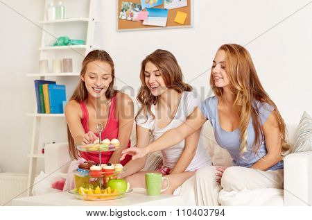 friendship, people, pajama party and junk food concept - happy friends or teenage girls eating sweets at home
