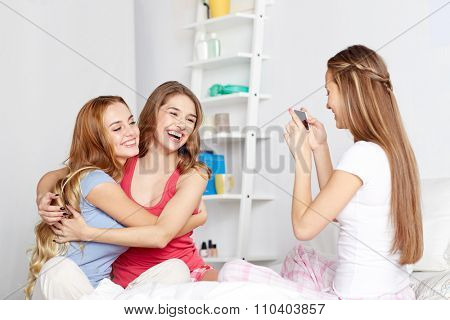 friendship, people, pajama party and technology concept - happy friends or teenage girls with smartphone taking picture at home