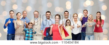 gesture, sale, shopping and people concept - group of smiling men, women and kids showing thumbs up and holding shopping bags over holidays lights background