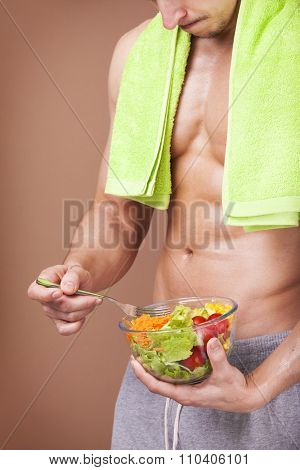 Muscled man holding a bowl of salad on brown background