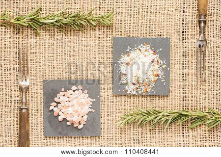 Two Kinds Of Salt On Dark Plates With Rosemary And Antique Forks