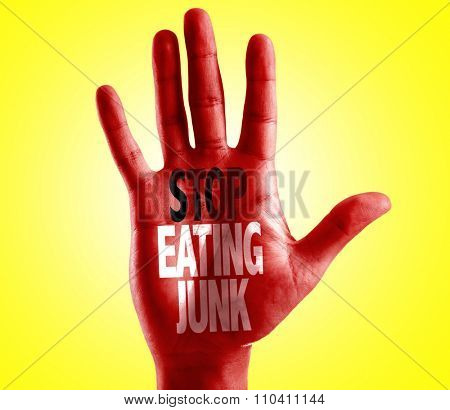 Stop Eating Junk written on hand with yellow background