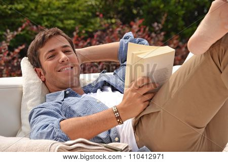 Young man portrait lying down on outdoor sofa ,reading a book and relaxing.
