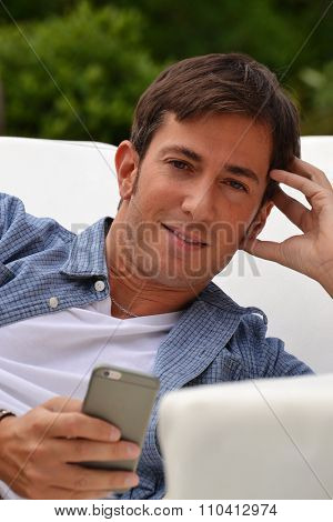 Young man chatting on smart phone lying down on outdoor sofa