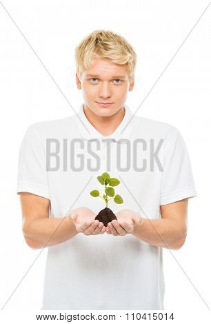 Young and handsome teenage boy holding soil with a plant on isolated background. Ecology concept.