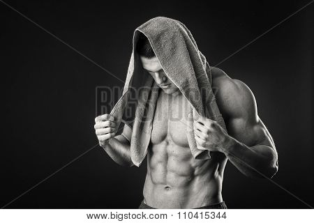 Fitness man holding a  towel against dark background