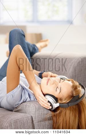 Junge Frau hören Musik Handauflegen Sofa