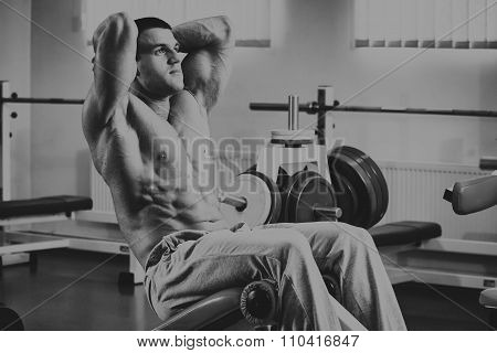 The lifter performs exercises back muscles at the gym.