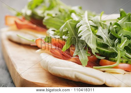 rustic sandwiches with ham arugula and tomatoes in pita bread on wood table