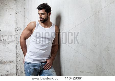 Brutal Man In A White T-shirt And Jeans Standing On The Cement Wall Background