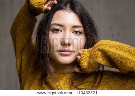 Close-up Portrait Of A Woman In A Soft Sweater Winter Brown On A Background Of A Cement Wall