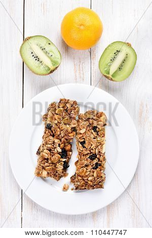 Cereal Bars On White Plate And Fruits