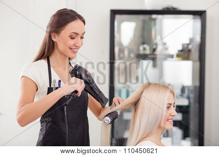 Attractive female hairstylist is working with joy