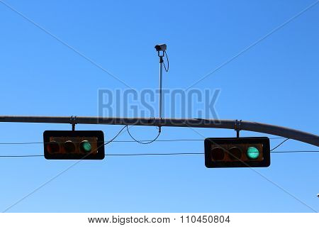 Green traffic light with surveillance camera