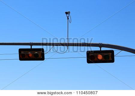Yellow traffic light with surveillance camera