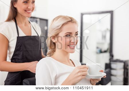 Beautiful blond girl is attending hairdressing saloon