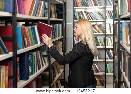 young woman with loose long blonde hair choosing a book between shelves in the library
