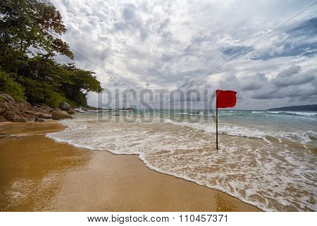 Secluded Beach With A Red Flag