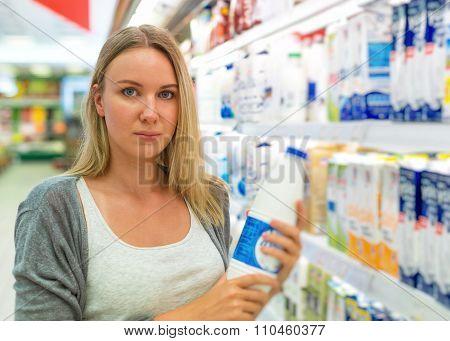 Woman Choosing Milk In Grocery Store.
