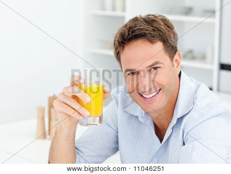 Handsome Man Drinking An Orange Juice In The Kitchen