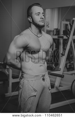 Athlete demonstrates muscles in the gym. Muscle tension of exercise performed