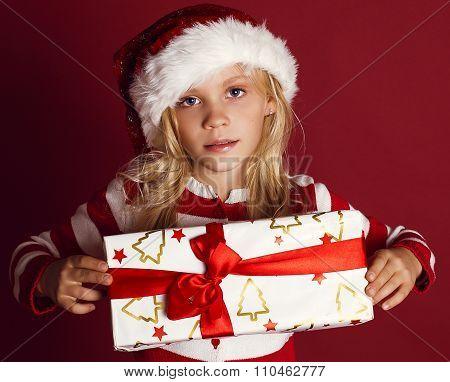 Cute Little Girl In Santa Hat Holding Christmas Present