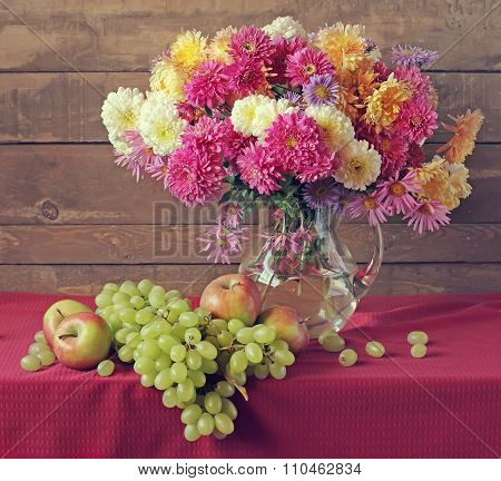 Still Life With Chrysanthemums In A Transparent Jug, Grapes And Apples.