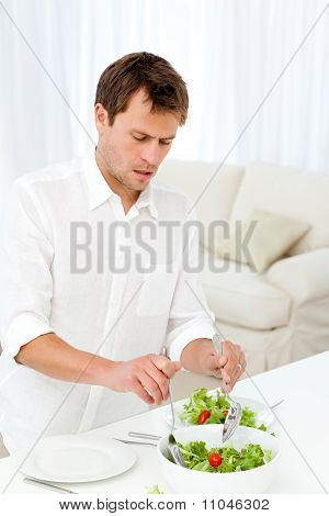 Single Man Serving Salad Standing At A Table
