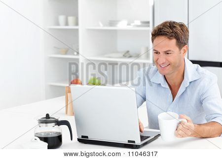 Happy Man Working On His Laptop While Drinking Coffee