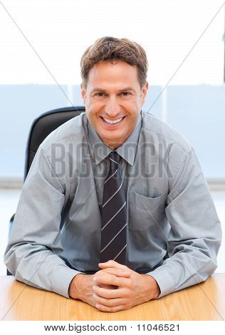 Happy Manager Sitting At A Table
