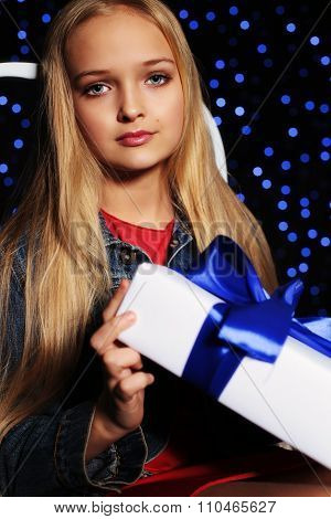 Cute Little Girl Whith Long Blond Hair Holding A Gift-box On The Backgroud Of Holiday Shining Lights