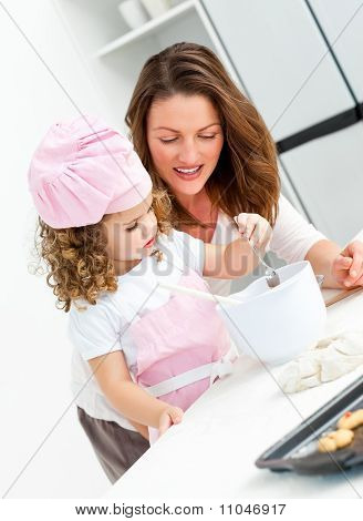 Little Girl With Her Beautiful Mother Cooking Together