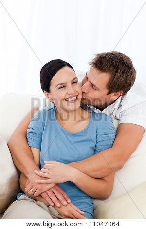 Happy Man Kissing His Girlfriend While Relaxing On The Sofa