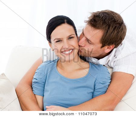 Lovely Man Kissing His Girlfriend While Relaxing On The Sofa